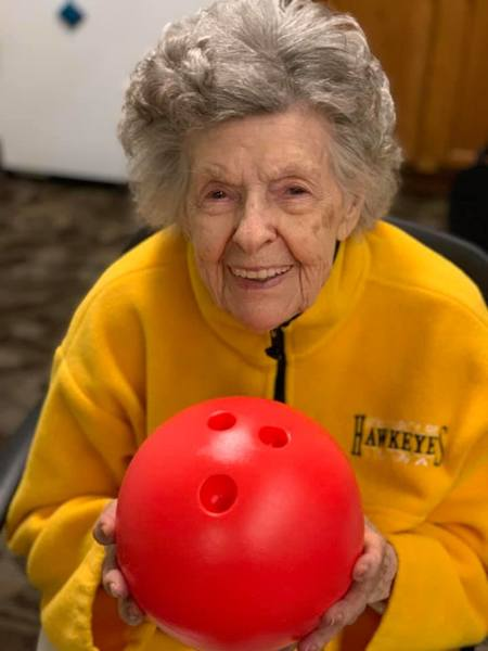 Elderly lady holding bowling ball and smiling.